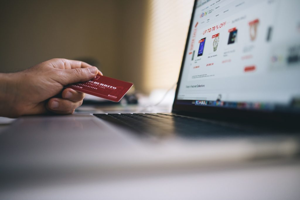 Image showing person using a laptop while holding a credit card